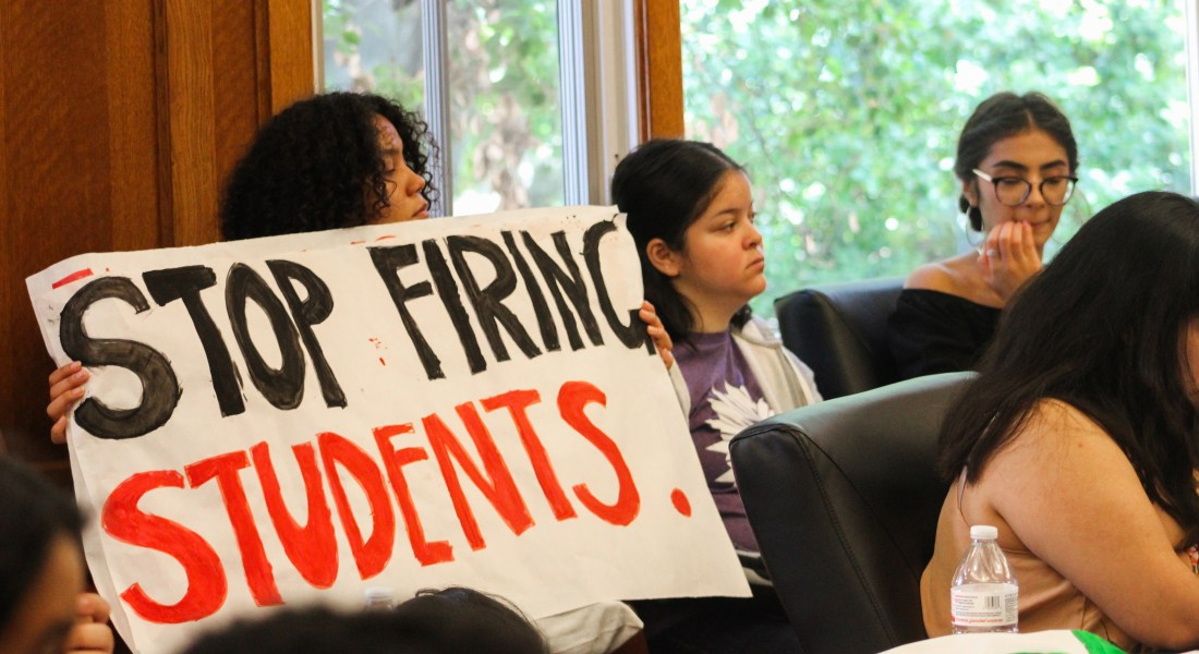 "A female college student stands holding a sign that reads ""Stop firing students"" during a sit-in at Pomona College."