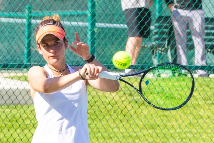 A player hits a backhand with her right hand, while her left is suspended near her left ear.