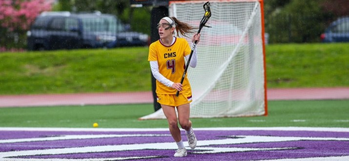 A woman in a yellow uniform holds a lacrosse stick with a ball in it.