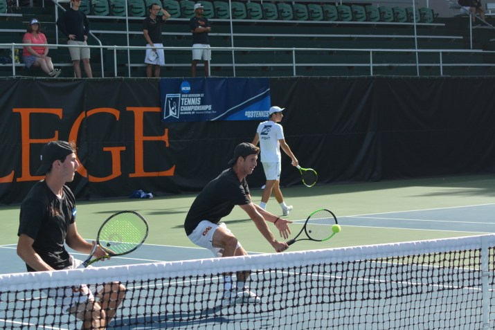Two men stand behind a tennis net, while one prepares to hit a tennis ball