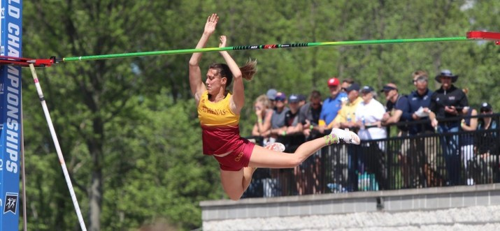 A woman in a red and yellow uniform tries to jump over a pole, while spectators in the background watch.
