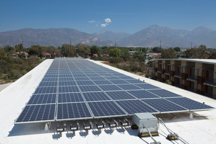A row of solar panels on top of a building.
