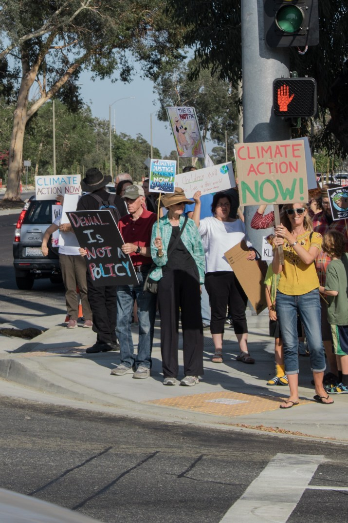 A crowd of people on the corner of a street wave signs advocating for climate change action.