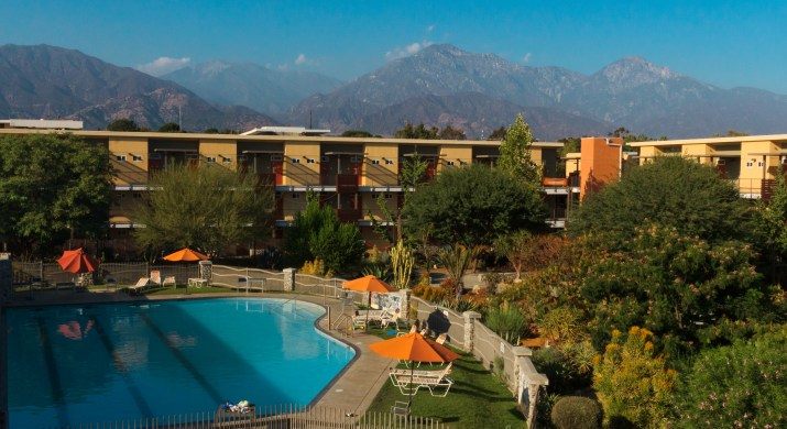 A pool is surrounded by furniture and buildings, with mountains in the background.
