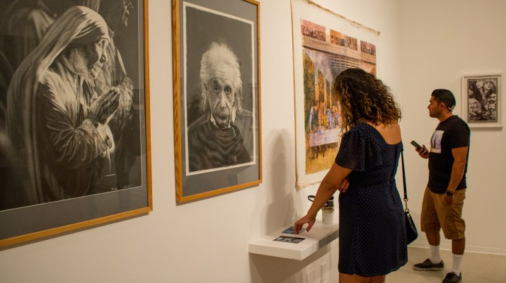 A man and a woman view drawings of Mother Teresa and Albert Einstein, along with a painting of The Last Supper, as part of the Disruption! art exhibit.