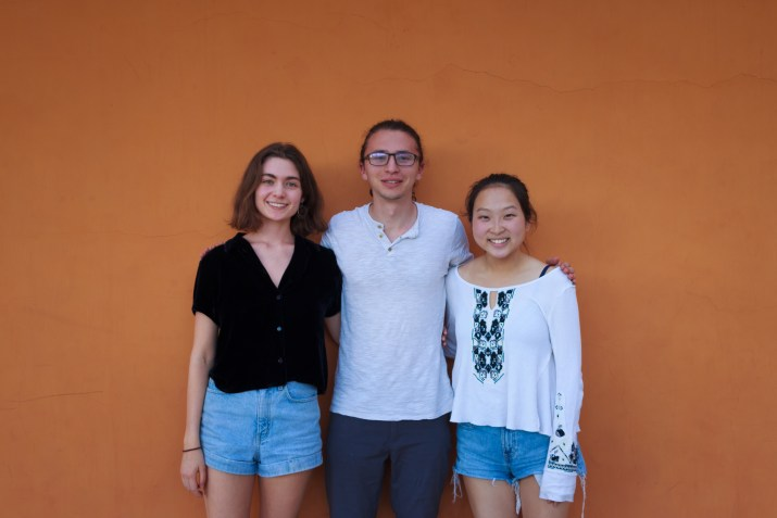 Two female students and one male student stand in front of an orange wall smiling