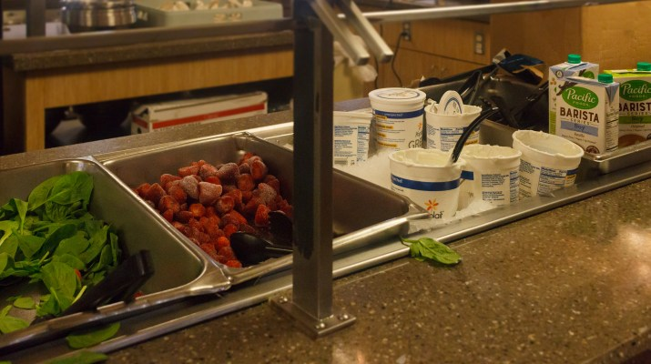 A smoothie bar with spinach, frozen strawberries and yogurt.
