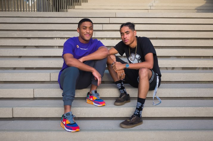 Two young male students sit crouched on outdoor steps, wearing colorful clothes and looking at the camera