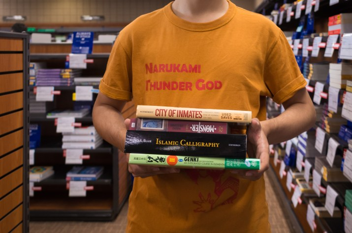 Person in yellow t-shirt holding a stack of textbooks.
