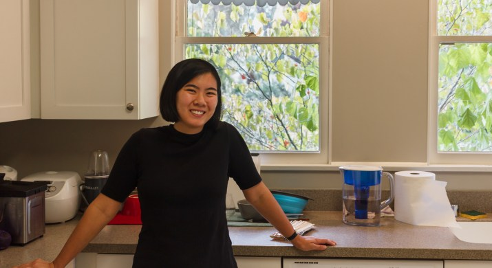 An East Asian female college student stands in a dorm kitchen smiling