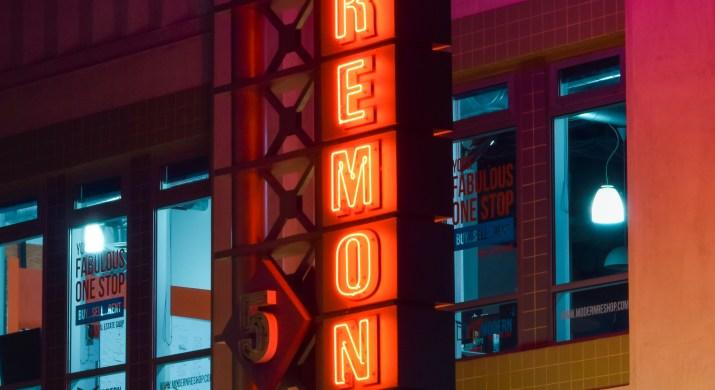 "The theatre's sign, which reads ""Laemmle's Claremont 5,"" illuminates a dark street in neon red lights."