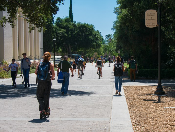 Several students, staff, and community members walk and bike along Pomona College's campus outside of Bridges Auditorium.