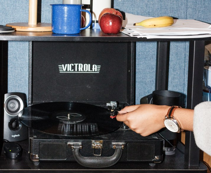A watch-clad hand puts a record on a black Victrola record player. A blue cup, red apple, peach, banana, and newspaper are perched on a shelf above the record player.