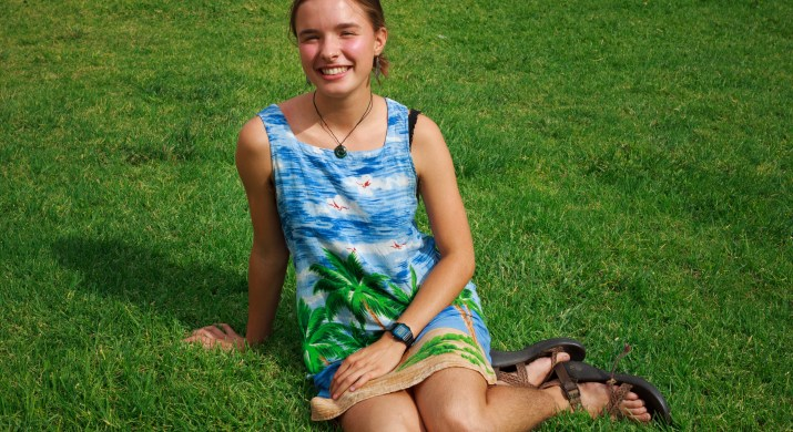 A white female college student sits on a grass lawn. She is wearing a dress with an ocean and palm tree pattern on it.