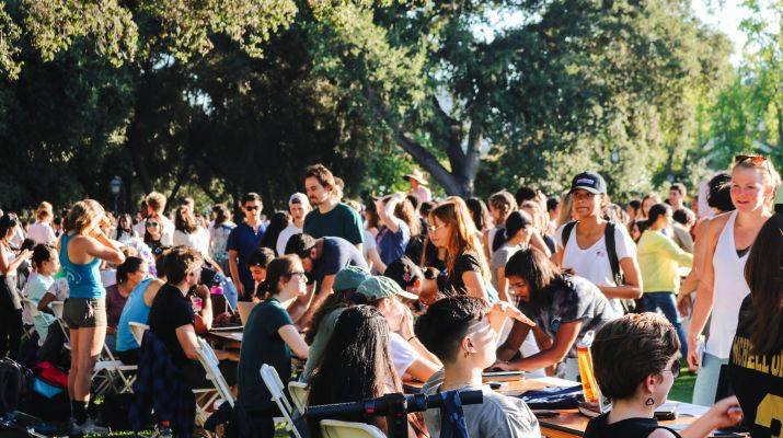 Hundreds of students walk around a grass field with many tables set up. Each table represents a college club or organization.