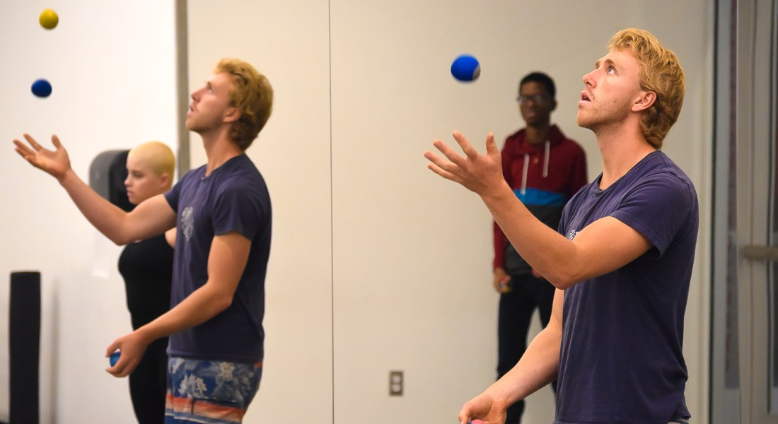 A male student juggles several blue and orange balls next to a mirror with his reflection.
