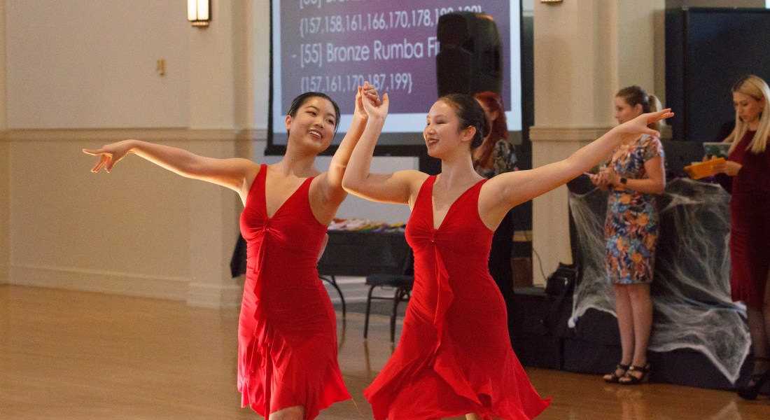 Two female college students in red dresses dance together.