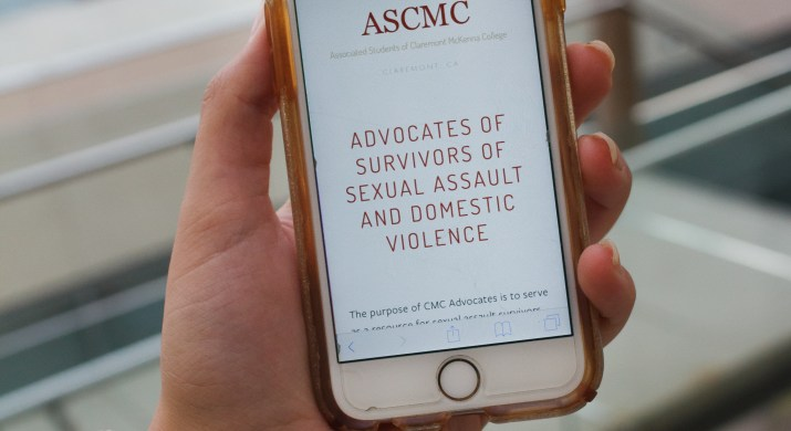 A female college student holds her phone. On the screen is the CMC advocates website and hotline number.