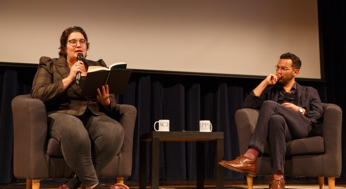 A woman sits on the left of the stage and reads from a book while a man sits on the other side of the stage listening intently.
