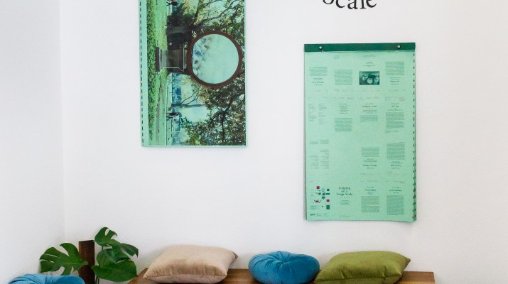"""The photo is of the inside of a building. Wooden benches line the wall with multi colored pillows scattered about. A few potted plants are on the ground and two posters are hung on the wall. The wall says """"Longing on a Large Scale."""""""