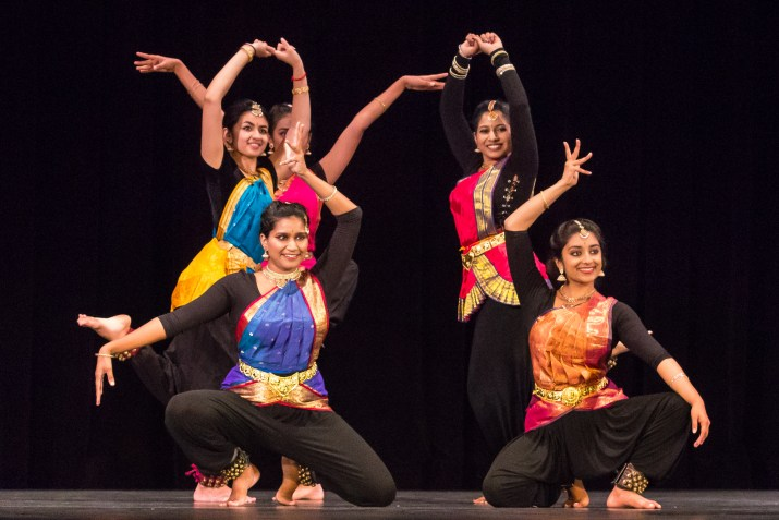 A group of female college students perform a dance in traditional Indian classical attire.