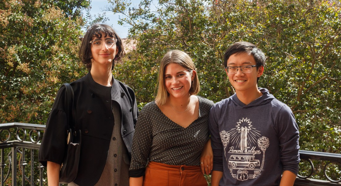 Three college students stand smiling at the camera in front of some trees.