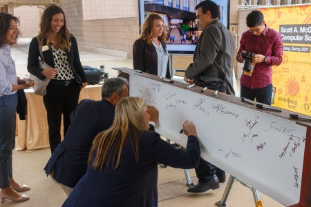 Several students stand around a white board while a man and a woman add their signatures to it.