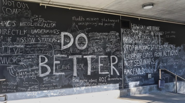 "A photo of a large, black board wall outside with messages written on it by college students. Some of the messages include ""DO BETTER,"" ""HMC's neoliberalism directly undermines the mission statement,"" ""Bragging about ROI [return on investment] demonstrates our unfailing commitment to amoral wealth."""