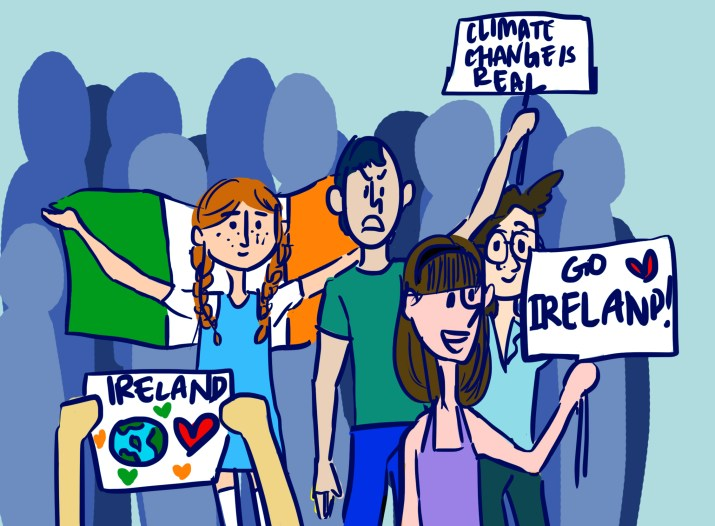 "Crowd of people at a protest holding up signs: one girl holds the Irish flag, another says ""Go Ireland"" while a third says ""climate change is real."""