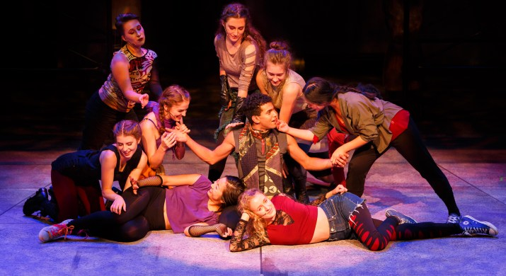 A male college student sits on a stage, surrounded by ten female actors.