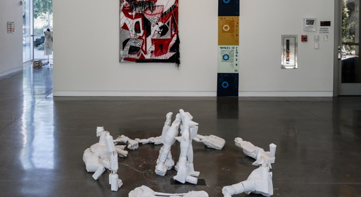 Various art projects are hung on the wall and placed on the floor in an art gallery.