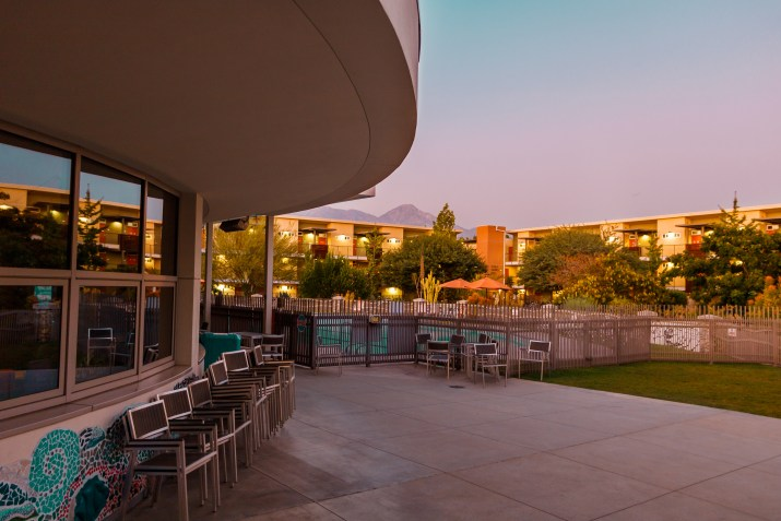 A cafe overlooks a pool at sunset.