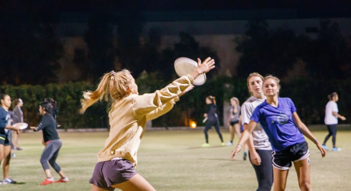 A female student stretches out her arms to catch a frisbee flying through the air.