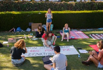 "Seven female college students sit around a banner on a grass lawn. The banner reads ""Carbon Commitment Signatories."""