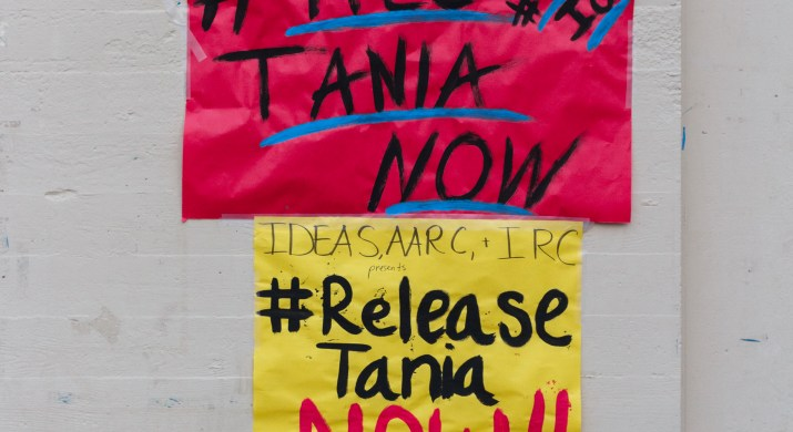"""A pink sign which reads """"#Free Tania Now"""" above a yellow sign which reads """"#release Tania now"""""""