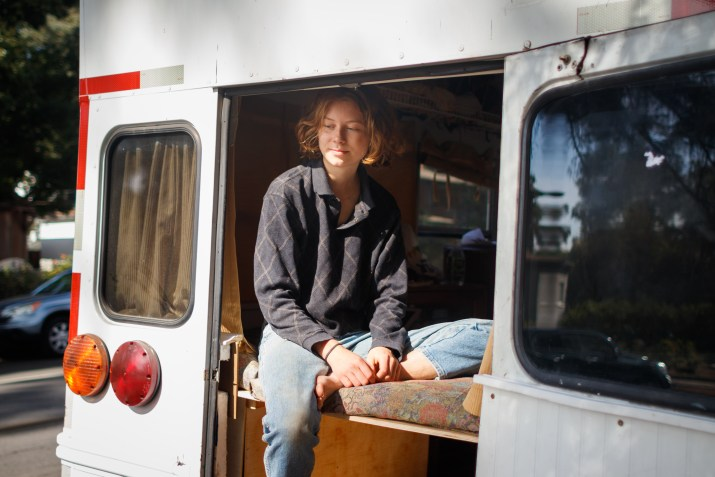Student Libby George, in a sweater and jeans, sits in the back of her renovated bus with the back doors swung open, looking off to the distance.