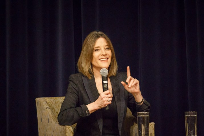 Marianne Williamson gestures to audience, holding up pointer finger and smiling with curtain in backdrop