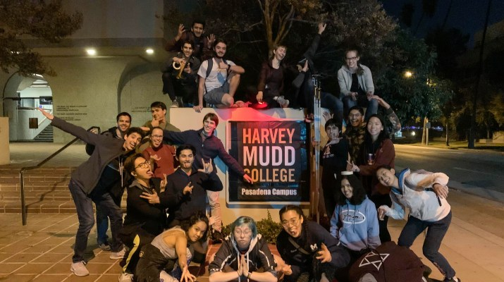 "A group of 20 college students stands around a poster that reads ""Harvey Mudd College Pasadena Campus"" smiling at the camera."