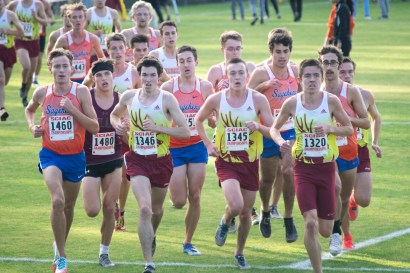 A pack of runners sprints down a field