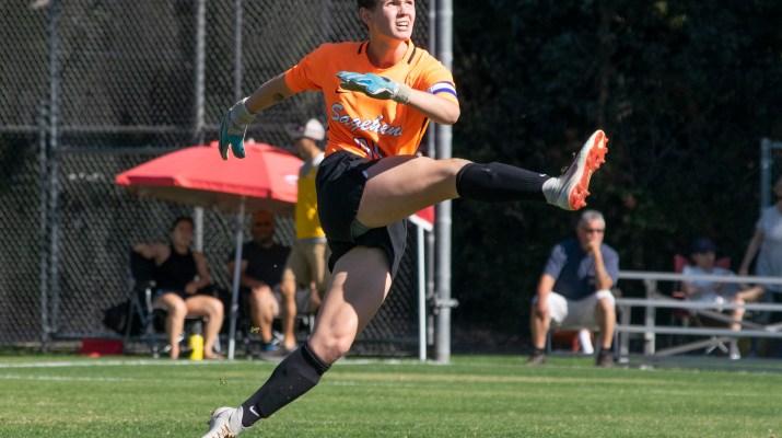 - A female athlete in an orange uniform kicks a ball.