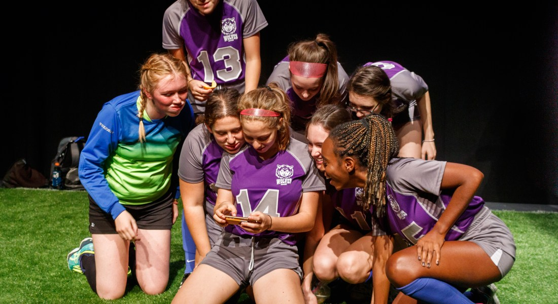 A group of 8 female college students in soccer uniforms huddles together to look at a phone screen.