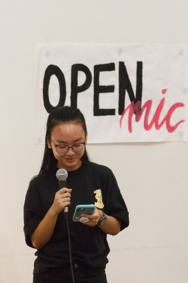 "A Chinese-american female college student holds a mic while reading from her phone. Behind her is a sign that reads ""OPEN Mic."""