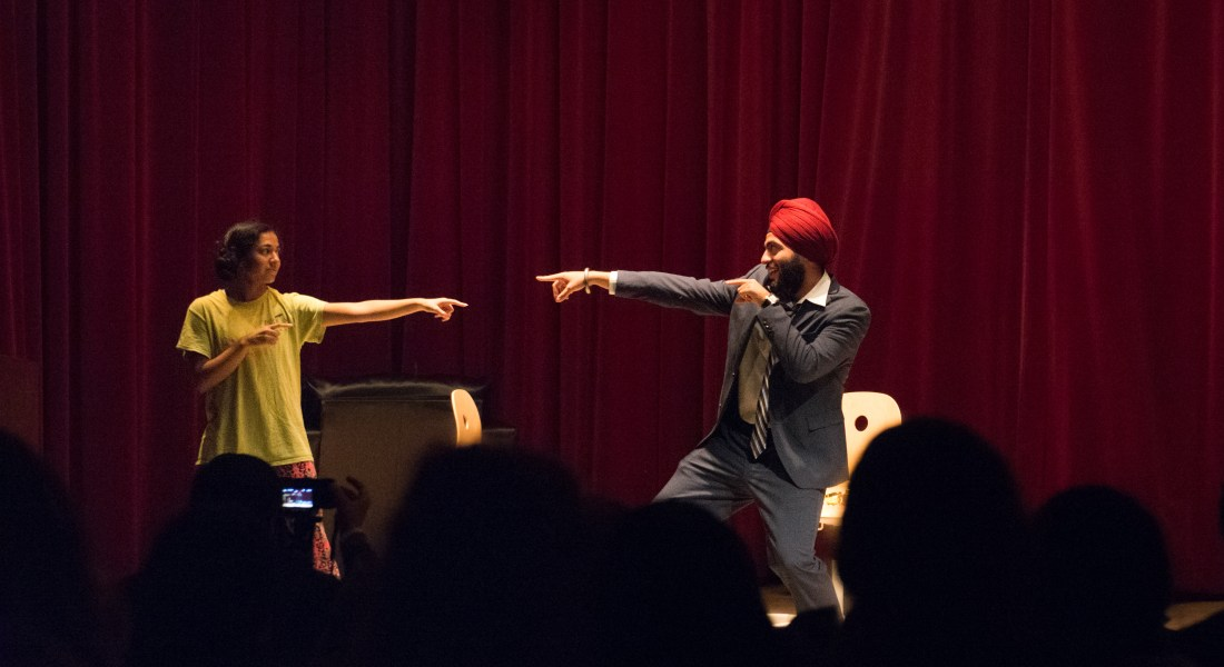 In front of a crowd of people, a woman in a yellow shirt and a man in a grey suit and red turban point at each other.
