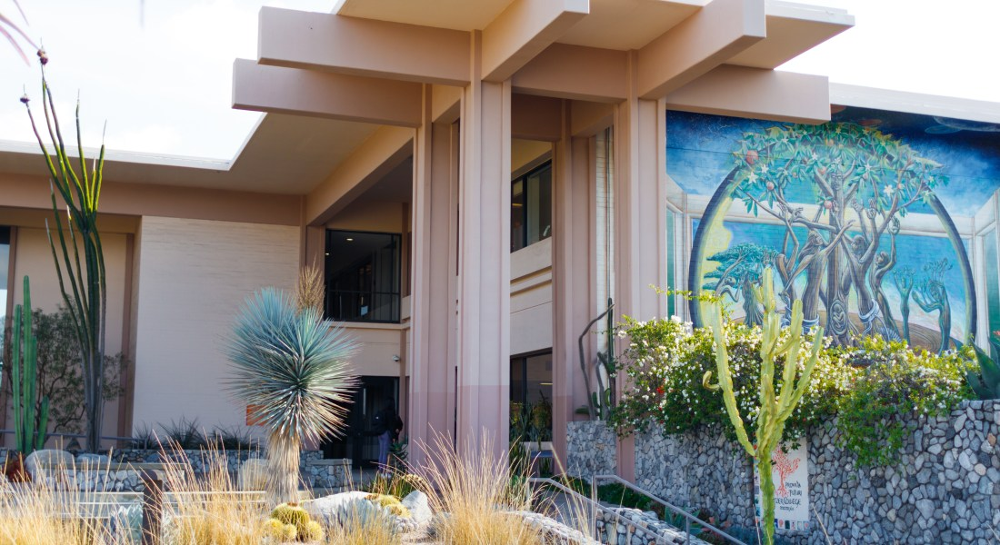 The outside of Pitzer College's dining hall surrounded by cacti.