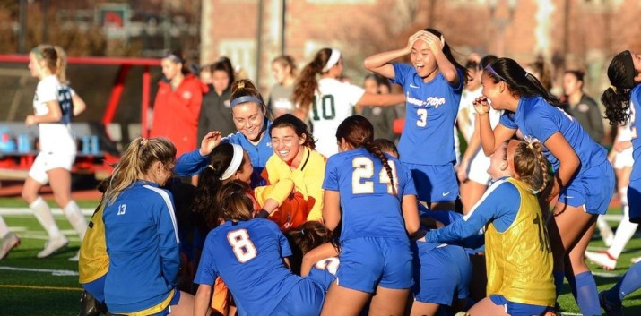 women in blue soccer uniforms celebrate a victory, yell and jump in air