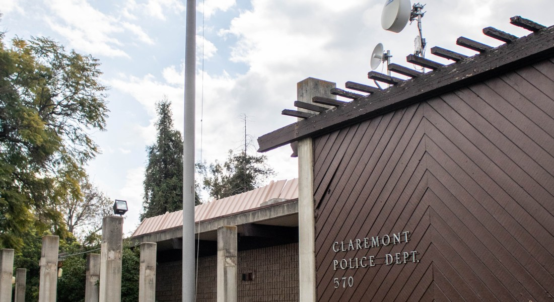 An American flag stands next to a short brown building called the Claremont Police Department.