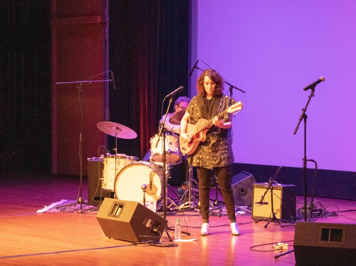 A women strums a guitar with a man playing the drums behind her.