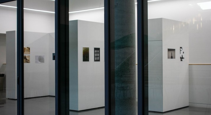 Photographs in a variety of colors are on white walls within an exhibit.