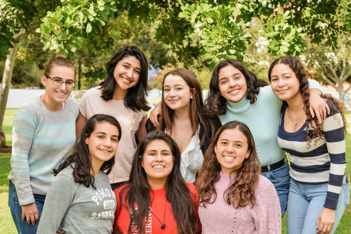 A group of women smile at the camera.