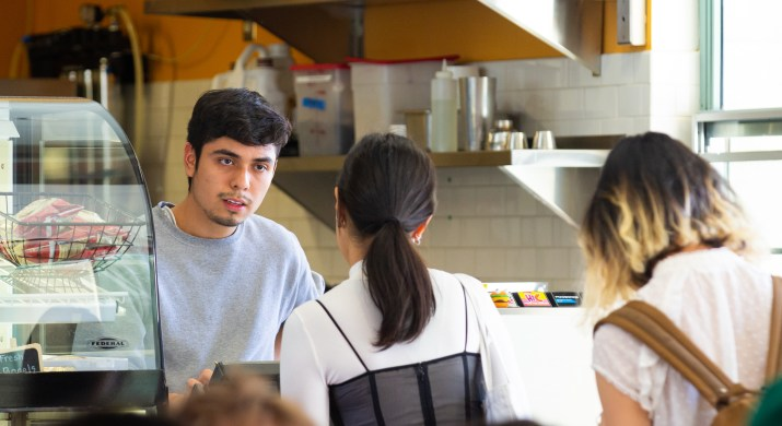 A man behind a cash register in the left of the image looks at the customer he is serving in the center of the image.